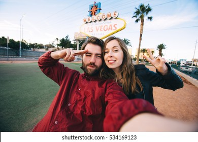 Happy young couple of tourists take selfie near Las Vegas Welcome sign. Two exited students take self portrait with a professional camera with Las Vegas billboard on the background, Nevada, USA