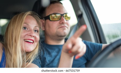Happy young couple travels in the car