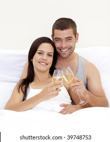 Happy young couple tusting with champagne in bed
