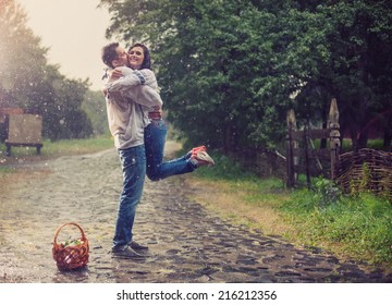 Happy young couple in Ukrainian style clothes hugging under rain