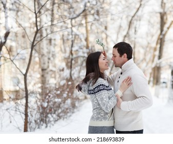 Happy young couple under mistletoe having fun in the winter park