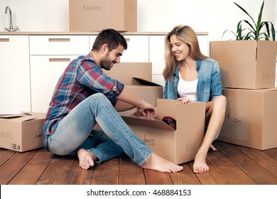 Happy young couple unpacking box with things while sitting on floor in new kitchen