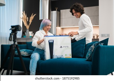Happy young couple unpacking brand new gaming console Sony Playstation 5 at home. Moscow - November 28 2020.