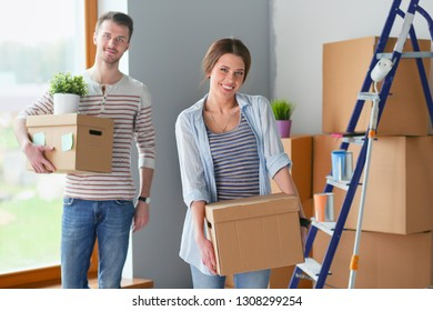 Happy young couple unpacking or packing boxes and moving into a new home. Happy young couple