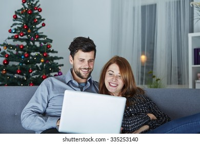 happy young couple use or watch something on laptop pc for christmas on sofa