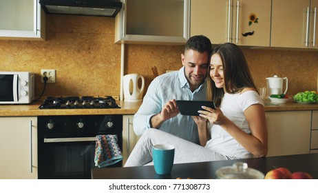 Happy young couple using digital tablet computer while sitting in the kitchen and having breakfast in the morning
