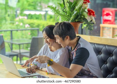 happy Young couple using laptop in a cafe. being  Choose a destination