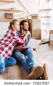 happy young couple using laptop and looking away in new house