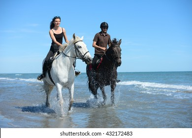 happy young couple vacation riding horses on the beach in a sunny summer day