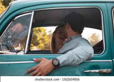 Happy young couple in vintage car, talking with each other