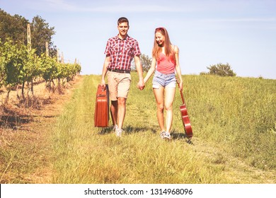 Happy young couple walking in a field  carrying suitcase and guitar on sunny summer day - Man and woman on country path - Concept of love and travel - Nostalgic filter look image