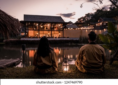 happy young couple walking with oil lamp over a bridge wearing kimono, man and woman at japanese onsen bath in Thailand walking outside during sunset
