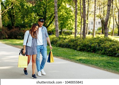 Happy young couple walking through the park after shopping