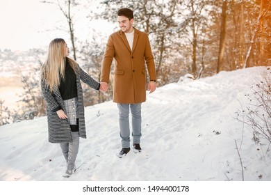 happy young couple walking through the park on a snowy day