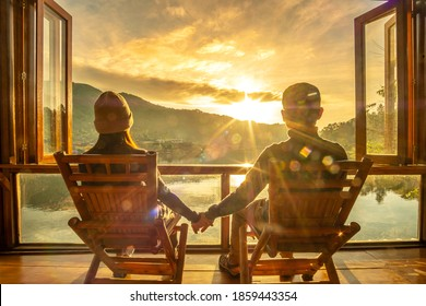 Happy young couple watching lake view at coffee shop in the morning sunrise, Ban Rak Thai village, Mae Hong Son province, Thailand. Travel, together and romantic concept