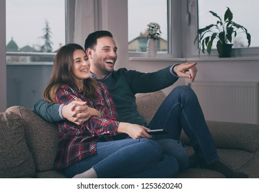 Happy young couple watching tv on sofa at home
