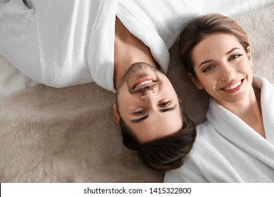 Happy young couple wearing bathrobes, top view. Visit to spa salon