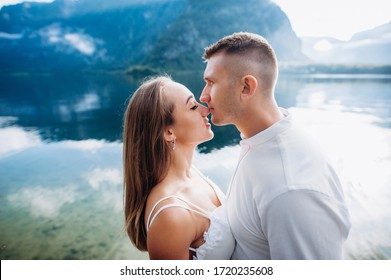 happy young couple in wedding dresses on a background of a lake and mountains