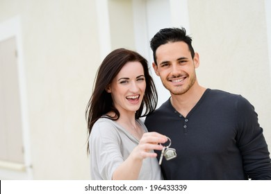 happy young couple welcome in their new house showing the door house keys