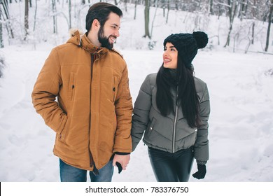 Happy Young Couple in Winter . Family Outdoors. man and woman looking upwards and laughing. Love, fun, season and people - walking in winter park. Stand and hold each other's hands