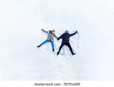 Happy Young Couple in Winter Park Lying On Snow. Making Snow Angel. top view