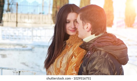 Happy young couple in the winter sunny park with blurred backround