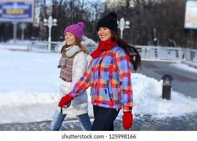 Happy young couple women in winter street