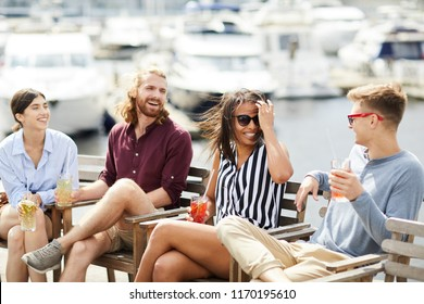 Happy young couples with drinks enjoying double date in outdoor cafe by waterside