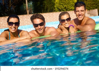 Happy young couples smiling in outdoor swimming pool at summertime.
