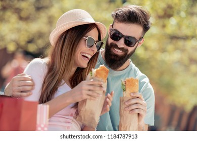 Happy young couple.They are laughing and eating sandwiches and having a great time.