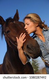 Happy young cowgirl hugging horse, eyes closed.