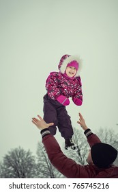 happy young dad in claret coat with little daughter in pink pattern coat smiling and playing outdoors in the winter park. Father throw up child. Concept of happy family