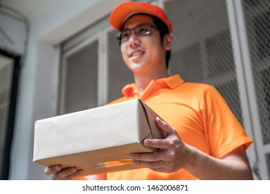 Happy young delivery man in the orange uniform standing with  parcel box to send to customers, focus on the parcel, delivery concept.