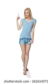 Happy young denim girl in shorts standing casually in full length, pointing to the side at blank copy space, against white background
