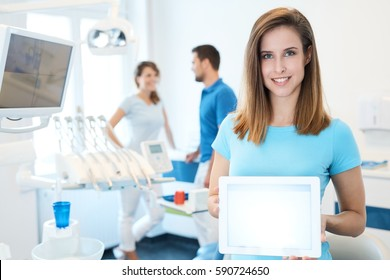 Happy young dental assistant holding tablet computer with blank screen.