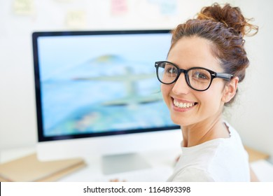 Happy young designer or editor looking at you with toothy smile with computer monitor on background