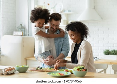 Happy young diverse parents have fun teach little biracial daughter cooking, overjoyed multiracial family with small girl child preparing food making healthy salad for breakfast in kitchen together