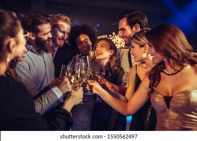 Happy young drinking champagne in the nightclub
