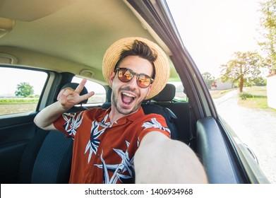 Happy young driver taking a selfie inside a car at vacation - Cheerful man at holiday rent a car at summer