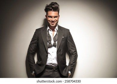 Happy young elegant business man smiling while holding both hands in his pockets.
