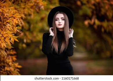 Happy young elegant woman in park on autumn day. Cheerful beautiful girl in black wear and hat outdoors among yellow leaves on beautiful fall day