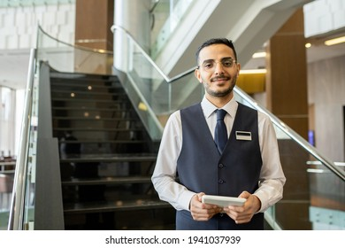 Happy young elegant worker of contemporary hotel using tablet while standing against staircase and looking at you inside lounge