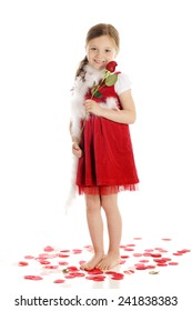 A happy young elementary girl holding a long-stemmed rose and surrounded by rose petals -- all in red and white.  On a white background.