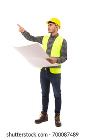 Happy young engineer pointing to something and holding a big paper, guy wearing caro shirt and jeans with yellow vest and yellow helmet, isolated on white background