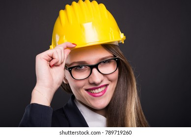 Happy young engineer woman with yellow helmet posing friendly on dark background