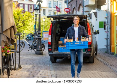 Happy young entrepreneur delivering wine and food by a local restaurant. Walking away from his back transport car toward the camera smiling.