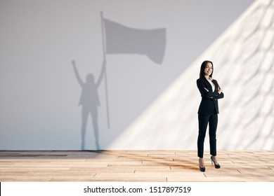 Happy young european businesswoman with flag shadow in white interior with sunlight. Leadership and success concept.