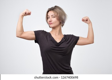 Happy young european woman showing her strong hand. I can do it concept