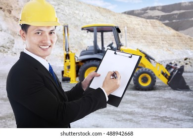 Happy young executive writing in clipboard and smiling to camera, a backhoe on the background, shot outdoors