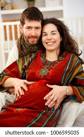 Happy young expectant couple sitting on floor in nursery looking at camera, smiling.